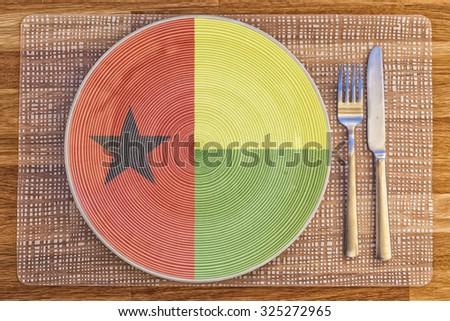 Dinner plate with the flag of Guinea Bissau on it for your international food and drink concepts. - stock photo