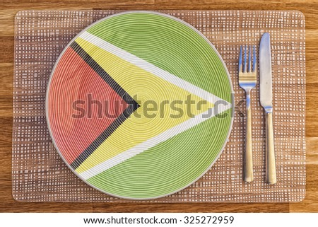 Dinner plate with the flag of Guyana on it for your international food and drink concepts. - stock photo