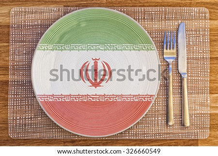 Dinner plate with the flag of Iran on it for your international food and drink concepts. - stock photo