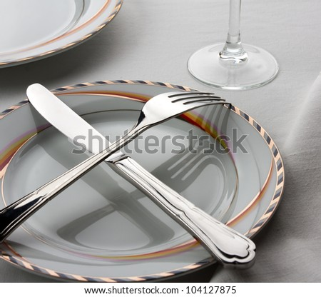 Dinner set. Crossed fork and knife on the plate - stock photo