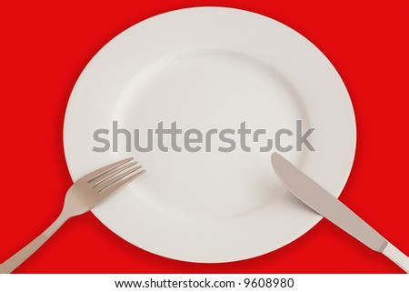 Dinner set - plate, knife and fork - isolated on red - stock photo