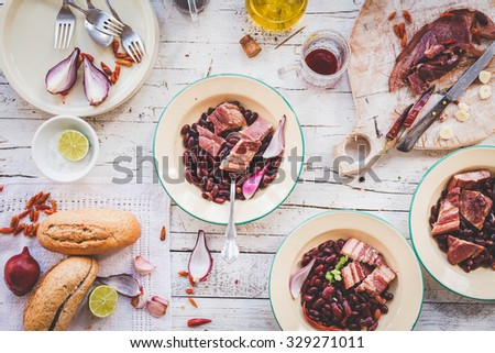 Dinner simple ideas with slow cooker recipe. Dish with red beans boiled garnish with pork meal portion in rustic bowls. Country styling. - stock photo