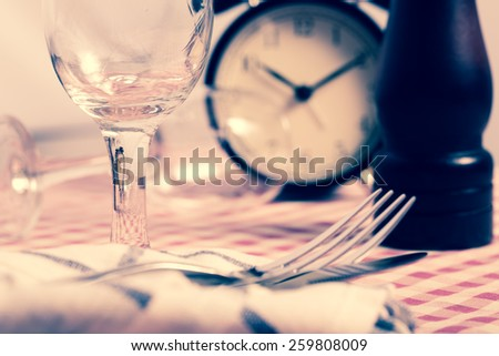 Dinner table set with alarm clock. Vintage filter. - stock photo