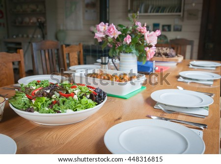 Dinner table, set with salad and food ready to be served and eaten.