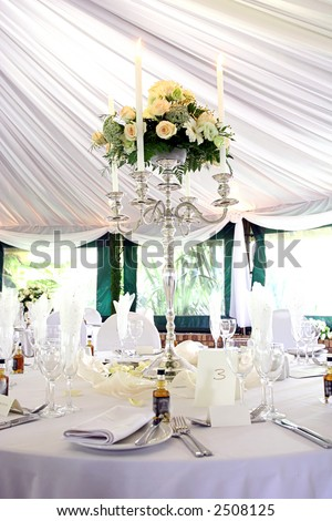Dinner table setting at a banquet with roses on a chandelier 2 - stock photo