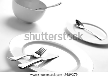 Dinner table setting of empty plates over white - stock photo