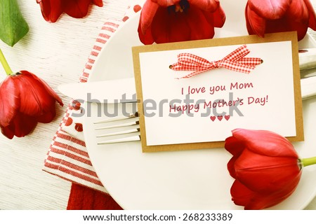 Dinner table setting with Mothers day message card and red tulips - stock photo