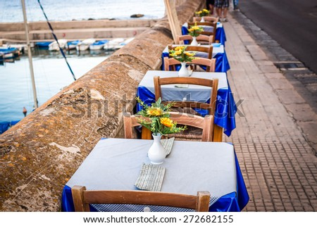 Dinner tables in Italian restaurant on brown parapet on the sea bay of Gallipoli  in Italy: fake yellow flowers with large petals and green leaves in white vase, White and blue gingham tablecloth - stock photo