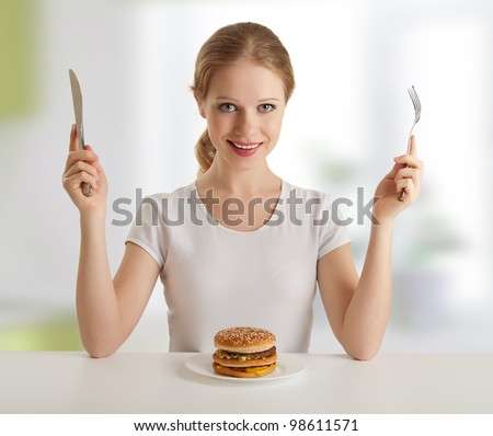 dinner time. pretty young woman with a knife and fork, and hamburger - stock photo
