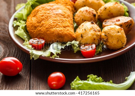 Dinner with chicken cutlets, cherry tomatoes, lettuce and baked potatoes. Food for dinner, closeup