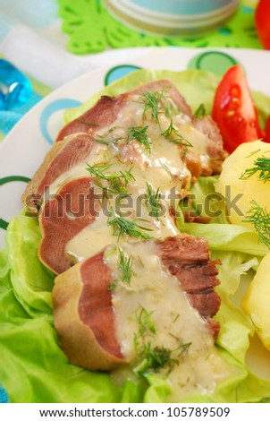 dinner with stewed pork tongue in horse radish and dill sauce, boiled potatoes,vegetables