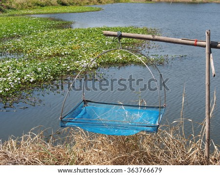 dip catcher fishing net homemade of square blue nylon nets and bamboo frame in shrimp farm THAILAND near a pond with smooth water surface on a sunny day  - stock photo