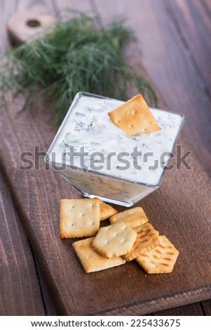 Dip sauce tzatziki  in bowl on wooden background. Selective focus, vertical. - stock photo