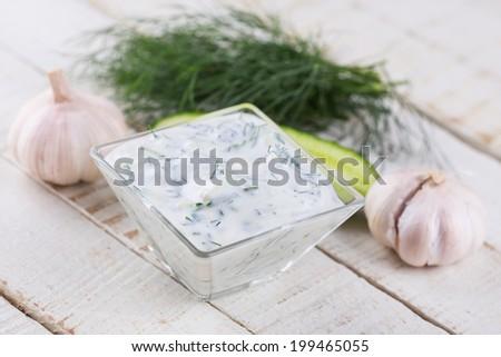 Dip sauce tzatziki with fresh yougurt, cucumber, garlic, herbs in bowl on wooden background. Selective focus, horizontal. - stock photo