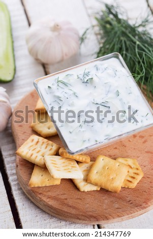 Dip sauce tzatziki with fresh yougurt, cucumber, garlic, herbs in bowl on wooden background. Selective focus, vertical. - stock photo