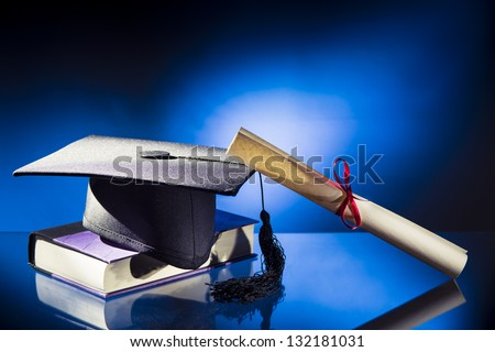 Diploma, Graduation hat and book on a blue background - stock photo