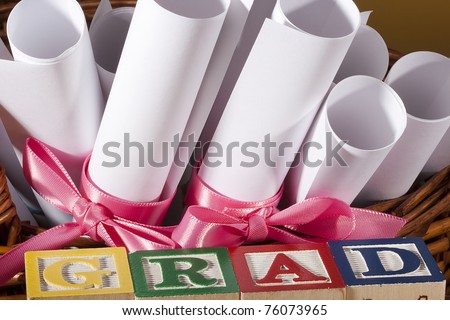 """Diploma tied with a ribbon, the text of the wooden blocks """"Grad"""". - stock photo"""
