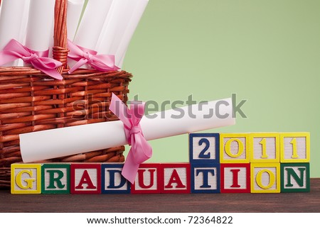 "Diploma tied with a ribbon, the text of the wooden blocks ""Graduation 2011"". - stock photo"