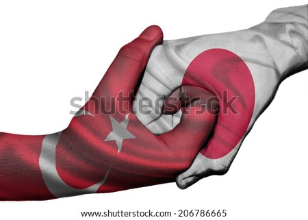 Diplomatic handshake between countries: flags of Turkey and Japan overprinted the two hands
