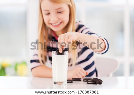 Dipping a cookie. Cute little girl dipping cookie in milk and smiling  - stock photo