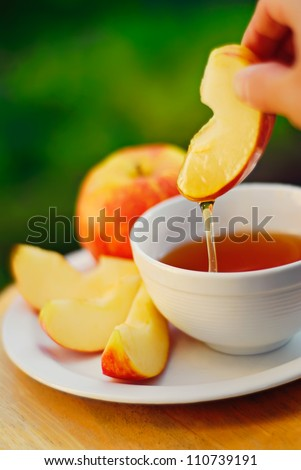 Dipping apples in honey for Rosh HaShana, the Jewish New Year - stock photo