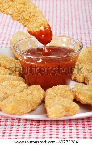 dipping chicken finger in BBQ sauce - stock photo