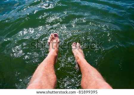 Dipping feet in water off a dock on a hot summer day
