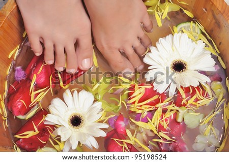 Dipping feet inside a bowl full of fresh flower, part of aromatherapy spa treatment - stock photo