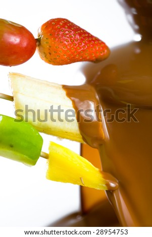 Dipping fruits into a Chocolate Fountain - stock photo