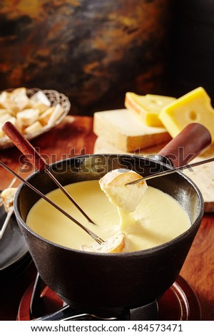 Dipping Into A Tasty Cheese Fondue With Bread On Long Handled Forks In A Close Up