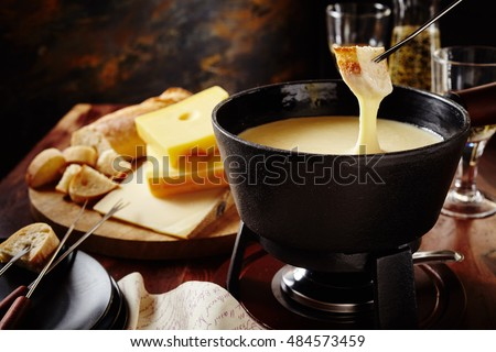 Dipping into a tasty traditional Swiss cheese fondue with bread on a fork, assorted cheese ingredients and white wine behind, close up view