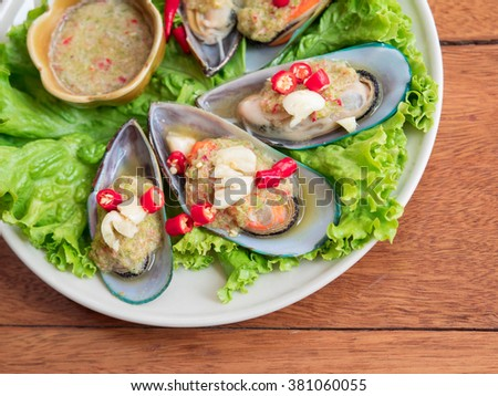 Dipping Spicy Sauce And Mussels Decorated With Fresh Vegetable - stock photo