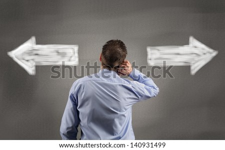 Direction choices and decisions for thoughtful businessman with left and right directional arrows - stock photo