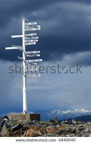 Direction pole with world cities signs on the top of Alaska's mountain - stock photo