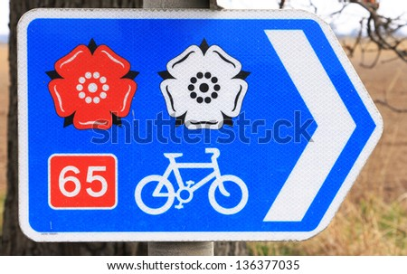 Direction sign for trans England cycle route showing the red and white roses of Lancashire and Yorkshire - stock photo