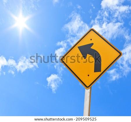 Direction sign- left turn warning on blue sky background - stock photo