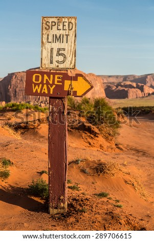 Direction signage in remote desert with stunning backdrop.