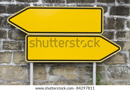 direction signs with wall in background. yellow signs. arrow shape - stock photo