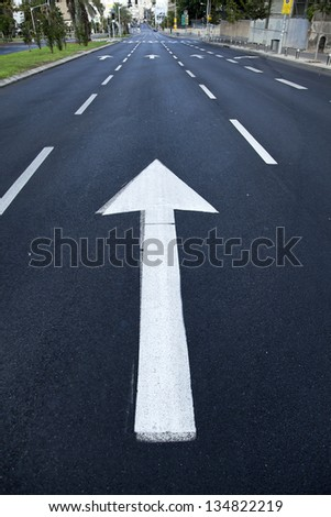 Directional arrow pointing forward on an empty street in Tel Aviv, Israel. - stock photo