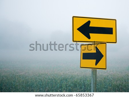 Directional arrow road signs pointing in different directions in the middle of the fog and haze. - stock photo