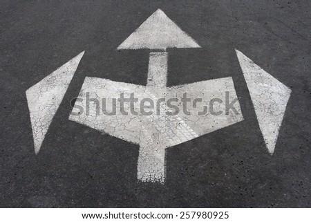 directional arrow signs on the asphalt road - stock photo