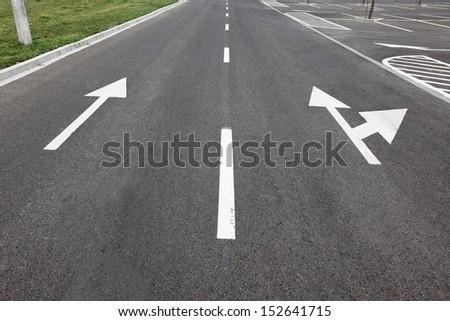 Directional arrows on the asphalt surface - stock photo