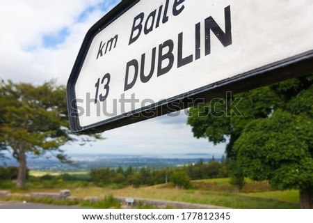 Directional road sign indicating Dublin 13 kilometres pointing towards Dublin in the distance - stock photo