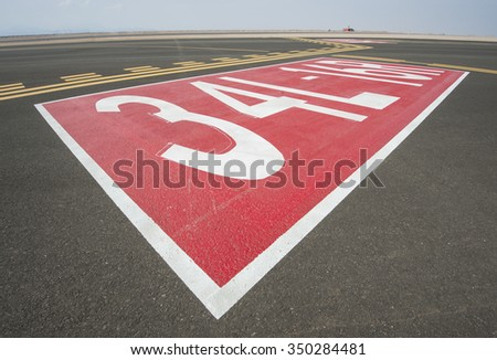 Directional sign markings on the tarmac of runway at a commercial airport - stock photo