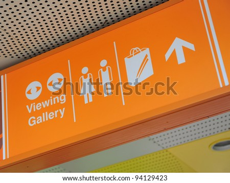 Directional signage indicating shopping areas, toilet and viewing gallery - stock photo