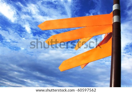 Directional signal against the blue sky with clouds - stock photo