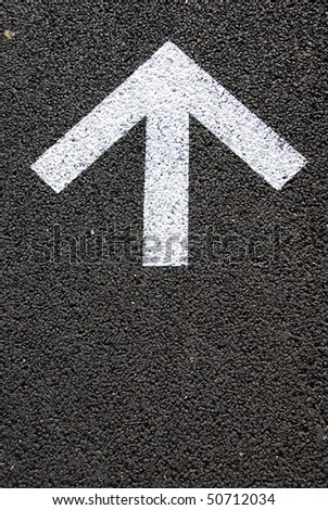 directional white arrow sign on the asphalt road