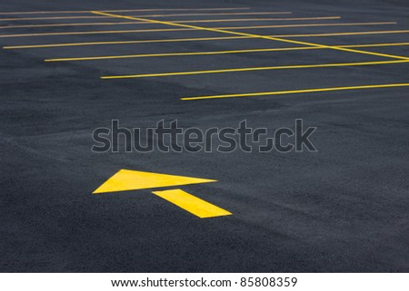 Directional yellow arrow symbol in a typical parking field - stock photo