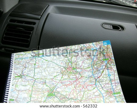 directions on a map in a car whilst traveling - stock photo