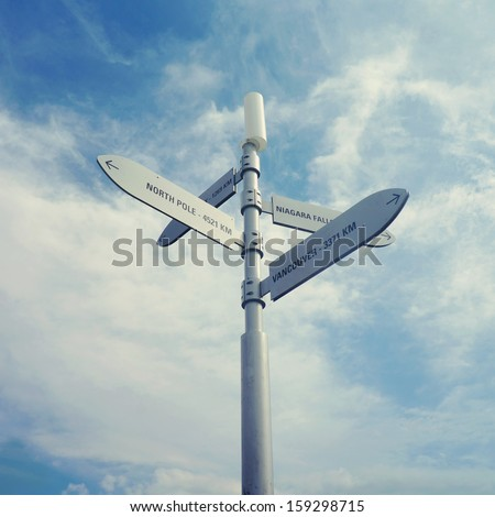 Directions to cities from Toronto over blue sky - stock photo